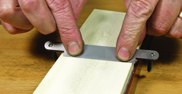 Posts straddle stone for sharpening blades of wooden shaves.