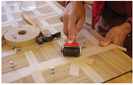 Working with veneer tape: A roller secures the tape and ensures a strong bond and a tight seam.