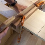 Saw perfect walls. The 16° guide is made from scrap and is clamped to the underside of the stool's top. An 8-point crosscut handsaw was used to make these four kerfs.